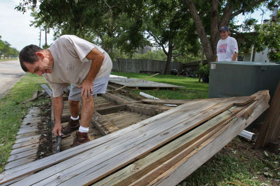 Steve Uren of Westgreen subdivision at the corner of Prospect Glen and Franz Road tries to dismantle his wooden privacy fence that was blown over by Hurricane Ike. Photo: Suzanne Rehak, For The Chronicle