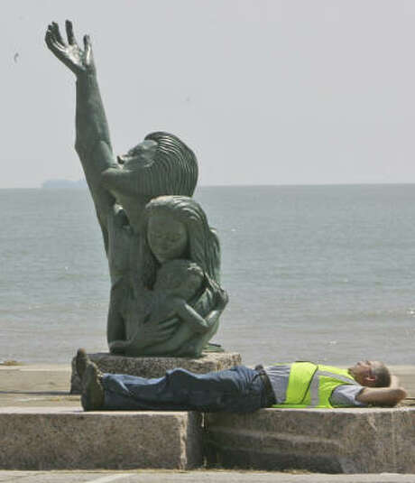 A worker takes a break on Galveston's seawall in front of a memorial statue to the killer hurricane of 1900. Photo: LM Otero, AP