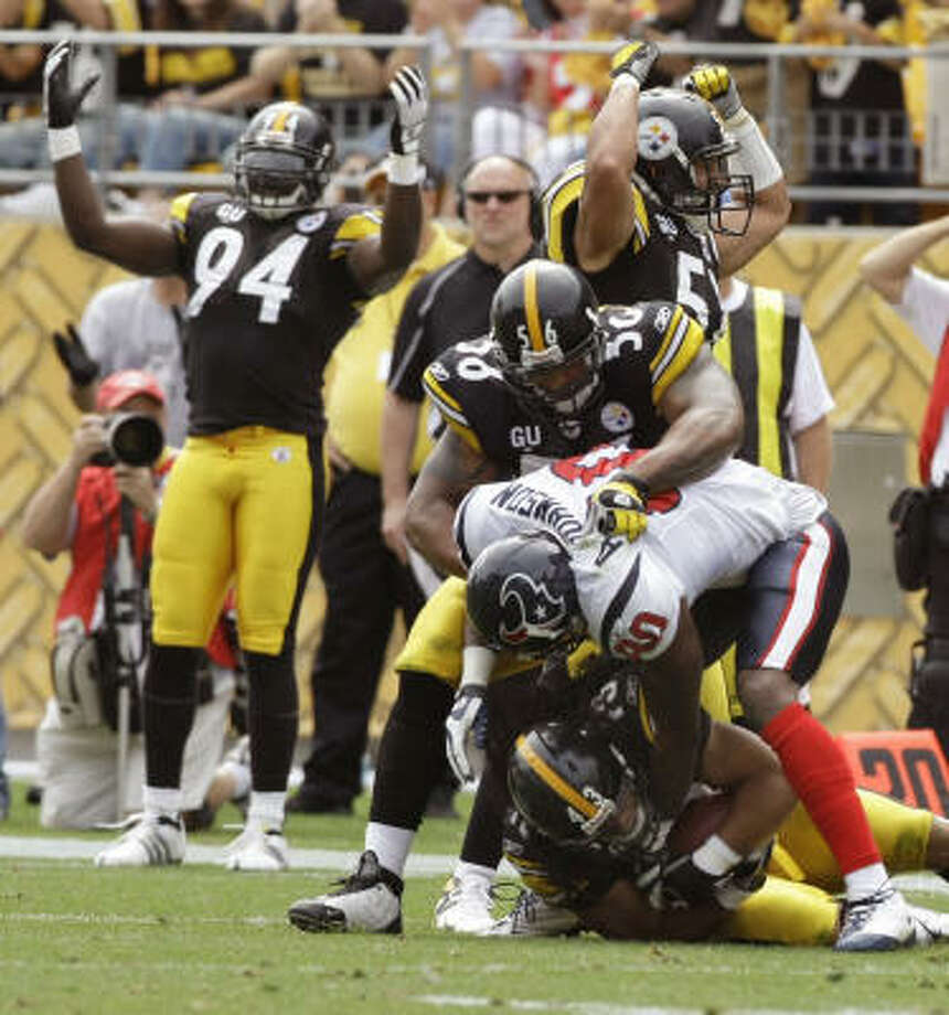 Pittsburgh Steelers safety Troy Polamalu (43) falls to the turf under Houston Texans wide receiver Andre Johnson (80) after grabbing an interception as linebacker LaMarr Woodley (56) grabs Johnson. The Steelers won 38-17. Photo: Brett Coomer, Chronicle