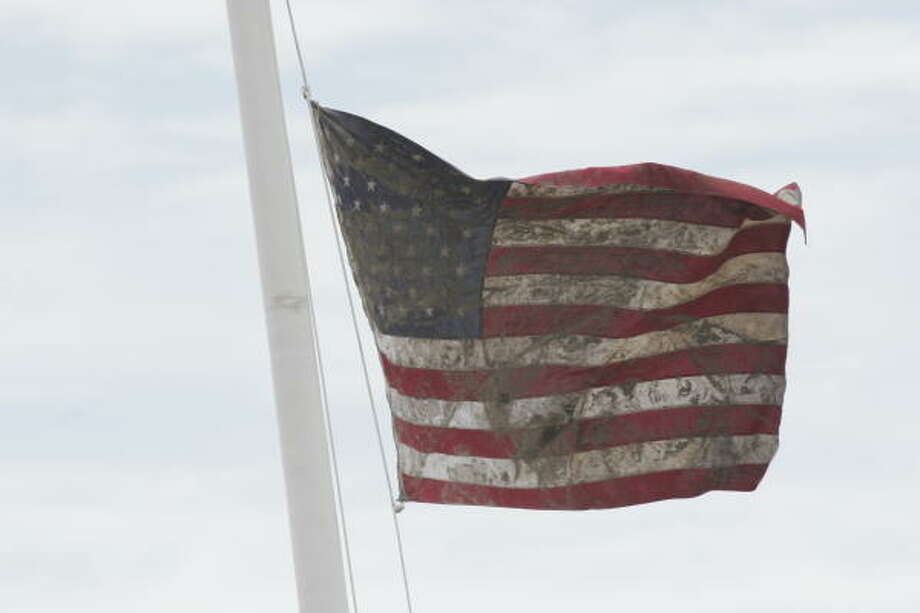 A muddy US flag flies over Gilchrist. Search and rescue teams raised the found flag in Crystal Beach where it helped helicopter pilots determine wind direction and velocity at the emergency LZ nearby. Photo: Shannon Tompkins, HOUSTON CHRONICLE