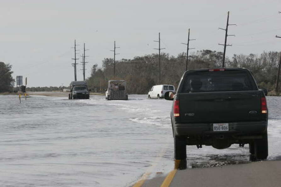 Ranchers negotiate the-still-flooded portions of State Highway 124 between Winnie and High Island as