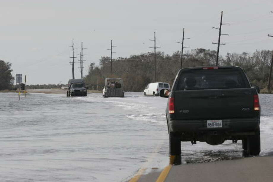 Ranchers negotiate the-still-flooded portions of State Highway 124 between Winnie and High Island as they work to collect livestock scattered by Hurricane Ike. Photo: Shannon Tompkins, HOUSTON CHRONICLE