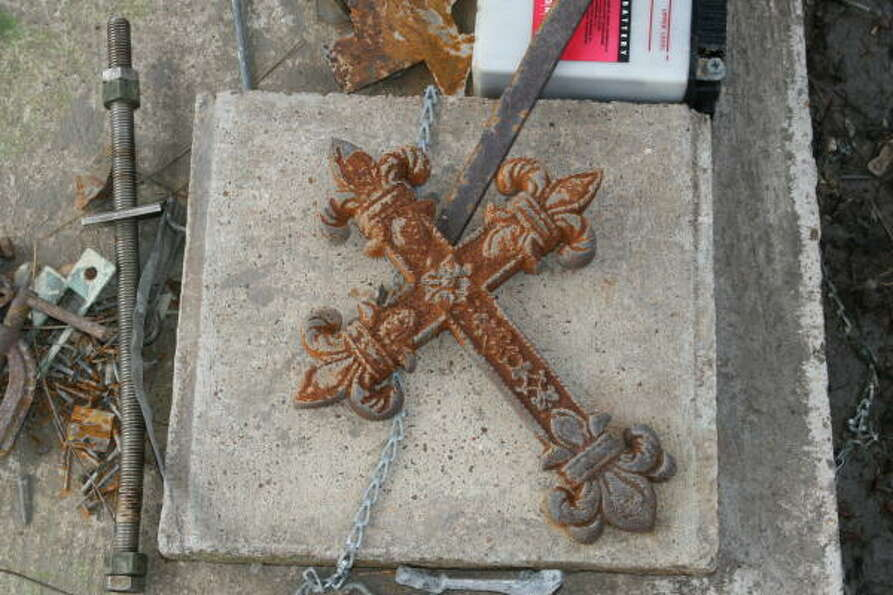 A metal cross, rusting from contact with Hurricane Ike's saltwater storm surge, sits atop a concrete