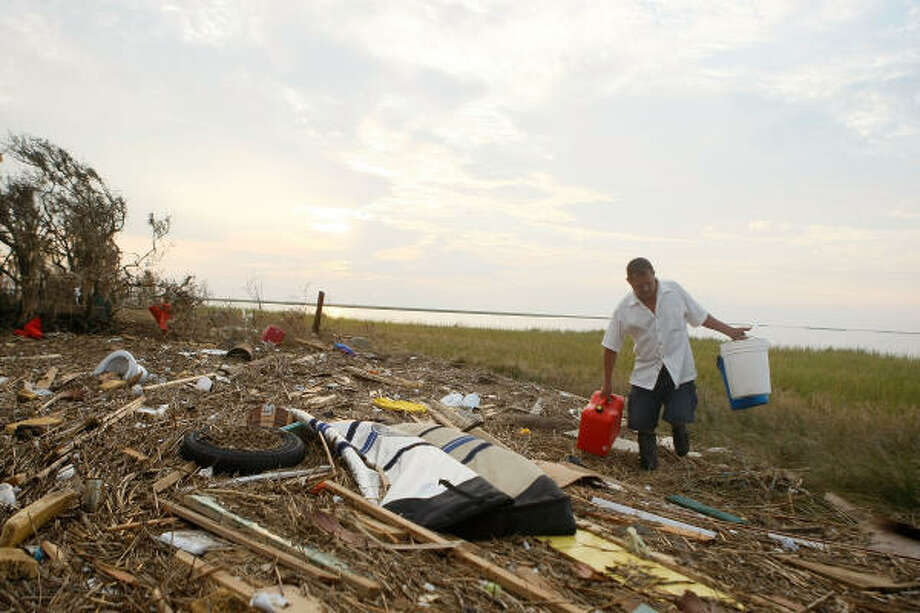 Mike Ryan finds a gas can and bucket to use while walking along the debris Sept. 18 in Bolivar. Photo: Mark Wilson, Getty Images