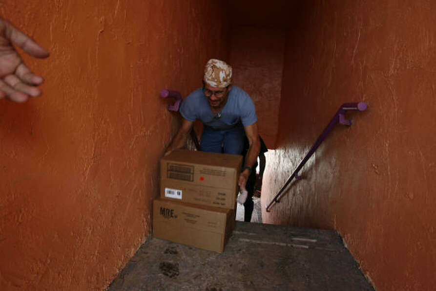 Michael Armond, 45, carries Meals Ready to Eat up the stairs at the Crystal Palace Resort on Wednesd
