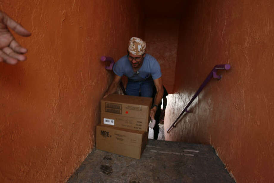 Michael Armond, 45, carries Meals Ready to Eat up the stairs at the Crystal Palace Resort on Wednesday in Crystal Beach. Photo: Sharon Steinmann, Chronicle