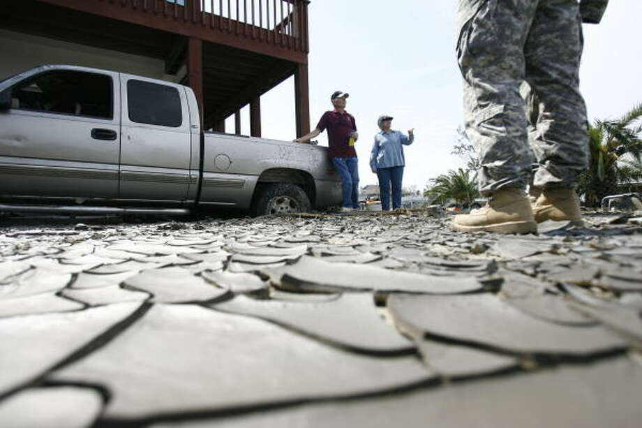 John R. and June Peveto talk to a Texas National Guard soldier in front of their stilted home on Wednesday in Crystal Beach. The couple decided Wednesday to finally leave and were waiting for local authorities to pick them up. Photo: Sharon Steinmann, Chronicle