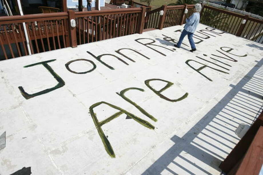 June Peveto, 59, walks over a painted sign she made in the hope that her children friends would see it from media reports. She and her 75 year old husband John R, Peveto rode out the storm in their stilted house in Crystal Beach. Photo: Sharon Steinmann, Chronicle