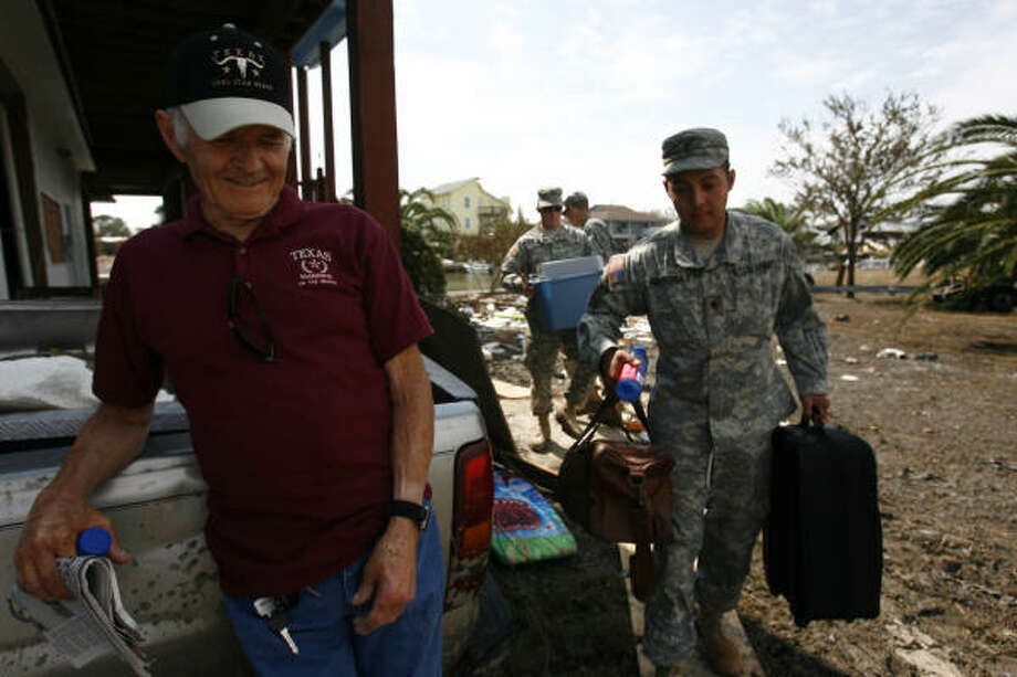 John R. Peveto, 75, smiles as Texas Army National Guard soldiers carry his belongings frm his stilted home Wednesday in Crystal Beach. Photo: Sharon Steinmann, Chronicle