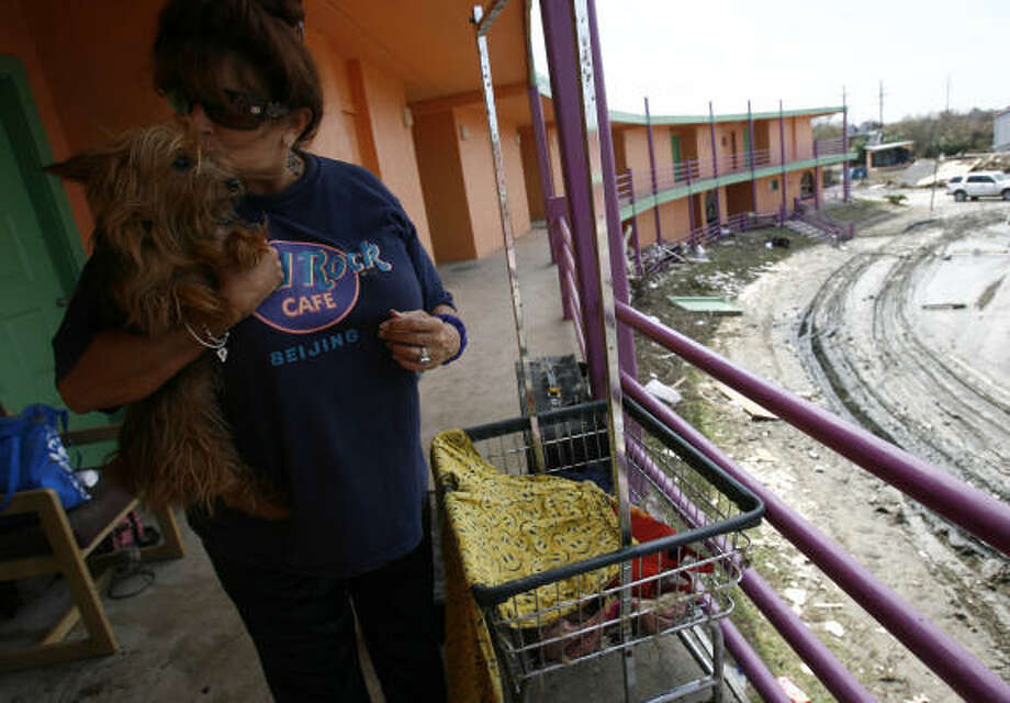 Anabel Pike, 52, kisses her Yorkie Abby near her room at the Crystal Palace Resort  on Wednesday in Crystal Beach. The Texas National Guard delivered Meals Ready to Eat and water to the five people who refuse to leave the hotel where they rode out the storm. Photo: Sharon Steinmann, Chronicle