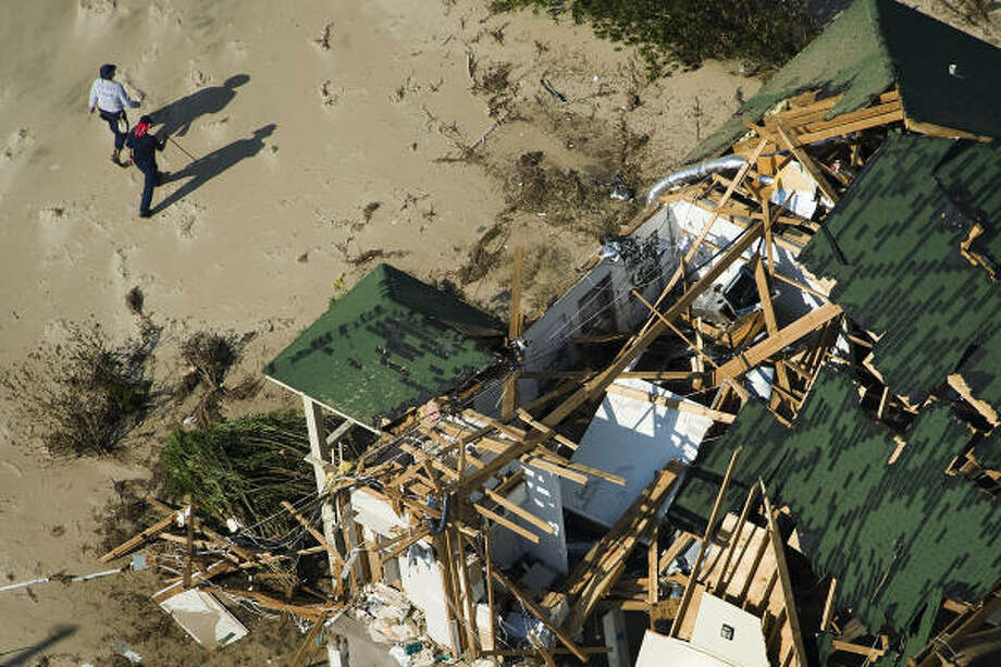 Searchers comb through houses damaged by Hurricane Ike Monday in Crystal Beach. Photo: Smiley N. Pool, Chronicle