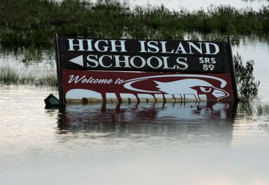 A sign promoting High Island schools is submerged in floodwaters Monday. Photo: Tony Gutierrez, AP