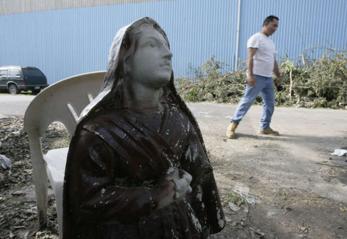 Ronald Mondragon, 43, walks past a statue of a Catholic saint toward his house, which was severely damaged by a large tree that fell on top of his house during Hurricane Ike.