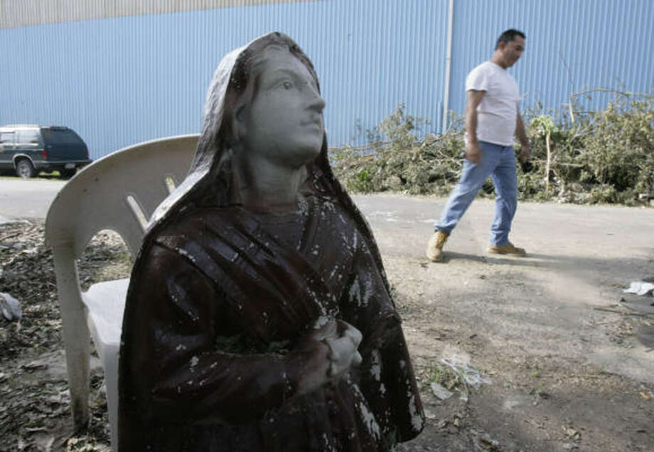 Ronald Mondragon, 43, walks past a statue of a Catholic saint toward his house, which was severely damaged by a large tree that fell on top of his house during Hurricane Ike. Photo: Julio Cortez, Chronicle
