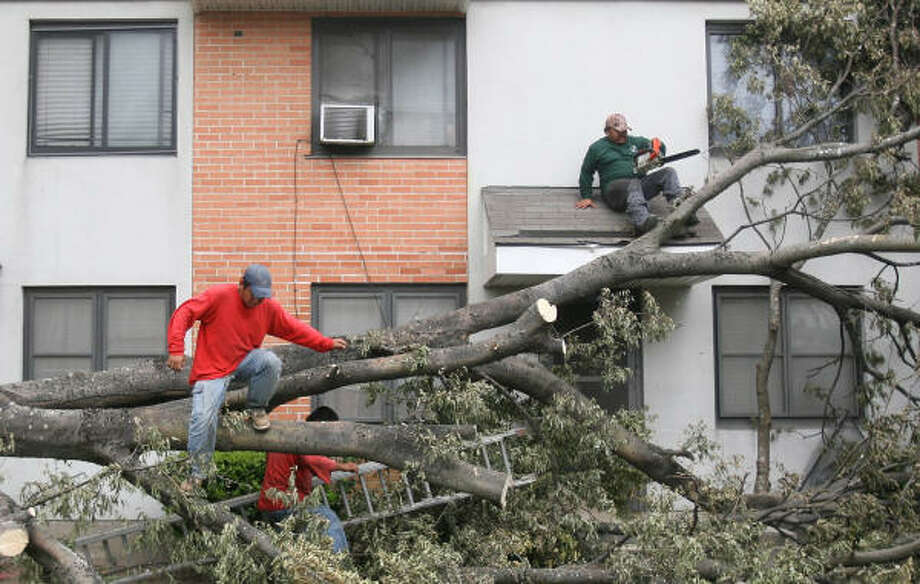 Alberto Ortiz and Jose Luis Rodriguez, of Green Planet Landscaping, remove the debris from a tree that collapsed in front of an apartment at Kelly Apartments on Friday, Sept. 19, 2008 in Houston. Photo: Mayra Beltran, Houston Chronicle