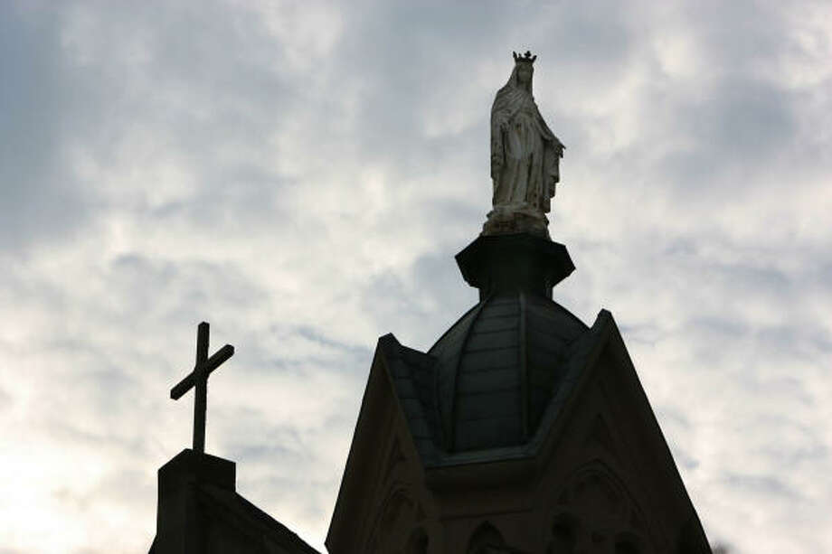 Statue of patron saint stands tall over St. Mary's Cathedral on Sept. 18. Despite flooding, the Cathedral survived Hurricane Ike. Photo: Mayra Beltran, Houston Chronicle