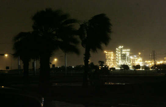 Palm trees along Highway 332 in Lake Jackson sway in the gusty winds from Hurricane Ike as the Dow Chemical Plant is seen hours before landfall on Friday in Surfside Beach. Photo: Julio Cortez, Chronicle