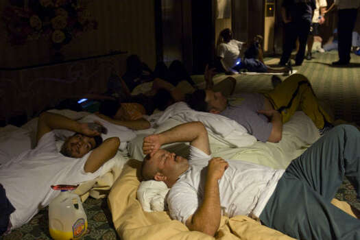 City of Galveston employees Michael Carachel, left, and Frank Perez bed down on the floor as they take shelter from Hurricane Ike in the San Luis Hotel in Galveston on Friday night. Photo: Brett Coomer, Chronicle