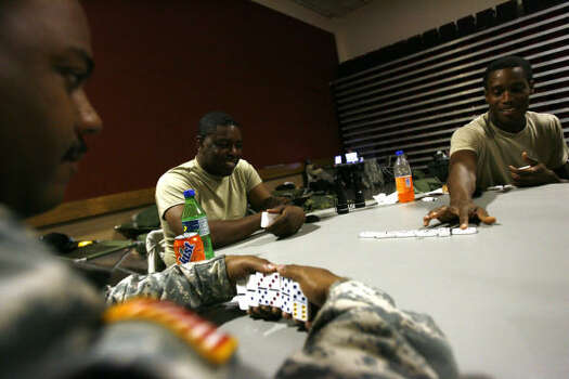 Texas Army National Guard soldiers pass the time playing dominoes at the Pasadena Convention Center as Hurricane Ike approaches. Photo: Sharon Steinmann, Chronicle