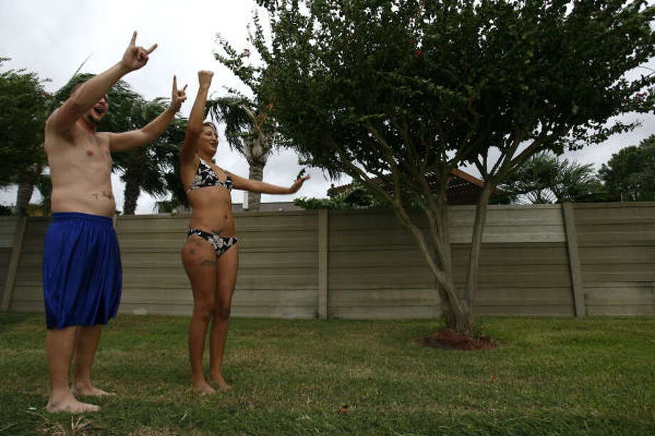 Ryan and his wife, Yoana Harrison, wave at passersby along Fairmont Parkway in Pasadena as they have a hurricane party at their house as the wind picks up on Friday. Photo: Sharon Steinmann, Chronicle
