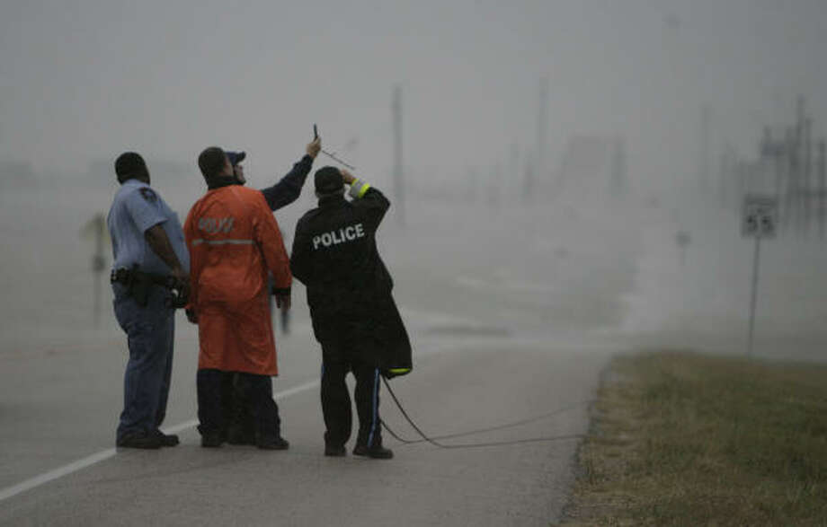 Surfside Beach officers look over the shoulder of a meteorologist from The Weather Channel while he takes wind readings on Highway 332 as gusty winds began to show force during Hurricane Ike's arrival. Photo: Julio Cortez, Chronicle