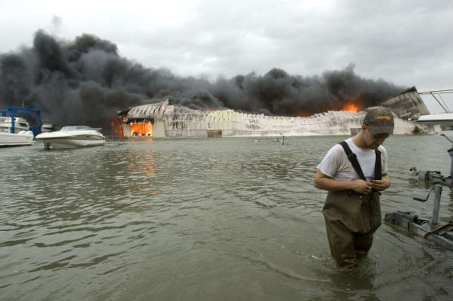 Chase Griffin of Galveston walks through floodwaters after checking on a boat storage facility that caught fire Friday in Galveston. Photo: Brett Coomer, Chronicle