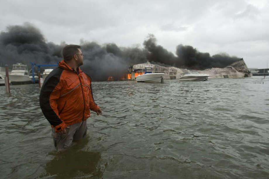 Michael Tate Gardner of Texas City walks through floodwaters after checking on a boat storage facility that caught fire. Photo: Brett Coomer, Chronicle