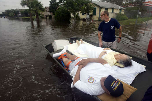 Galveston rescue workers bring in Frank Urbina and his wife, Celia, who were bedridden in their home on 57th Street, which filled with waist-deep water from Hurricane Ike's surge. Photo: Johnny Hanson, Chronicle