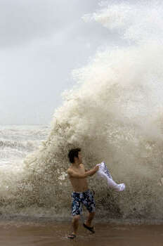 Sean Weng of Houston runs away from a wave on Galveston's seawall. Photo: Johnny Hanson, Chronicle