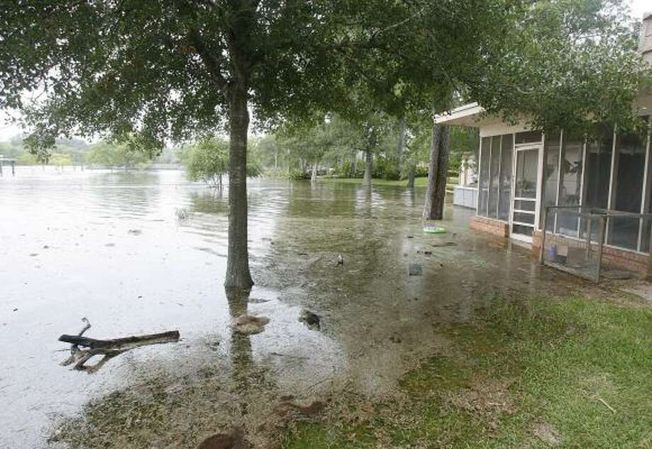 Rising water from Dickinson Bayou starts to creep into houses. Photo: Kevin M. Cox, AP / Galveston County Daily News
