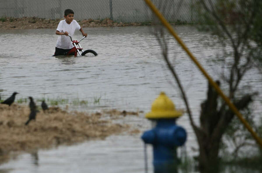 A Manchester youth navigates his bike through floodwaters. The neighborhood sits near the Houston Sh