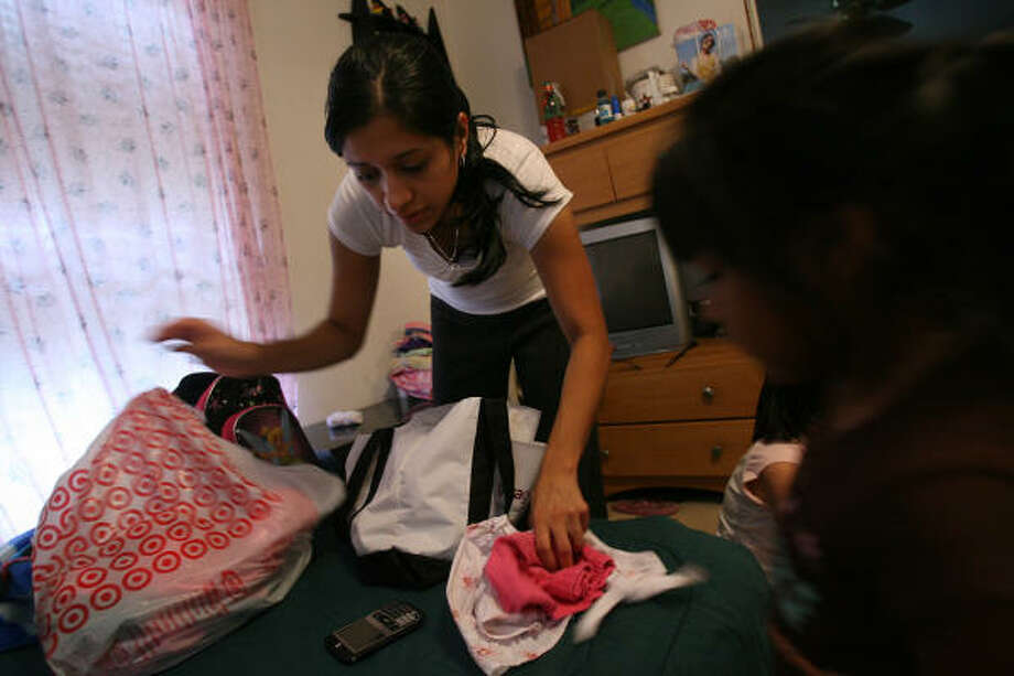 Manchester resident Stephanie Hernandez packs up clothes to leave her Manchester home while her daughter Jordan Martinez, 3, watches. They will ride out the storm at her grandfather's house along Lockwood instead of staying so close to the Houston Ship Channel. Photo: Mayra Beltran, Chronicle