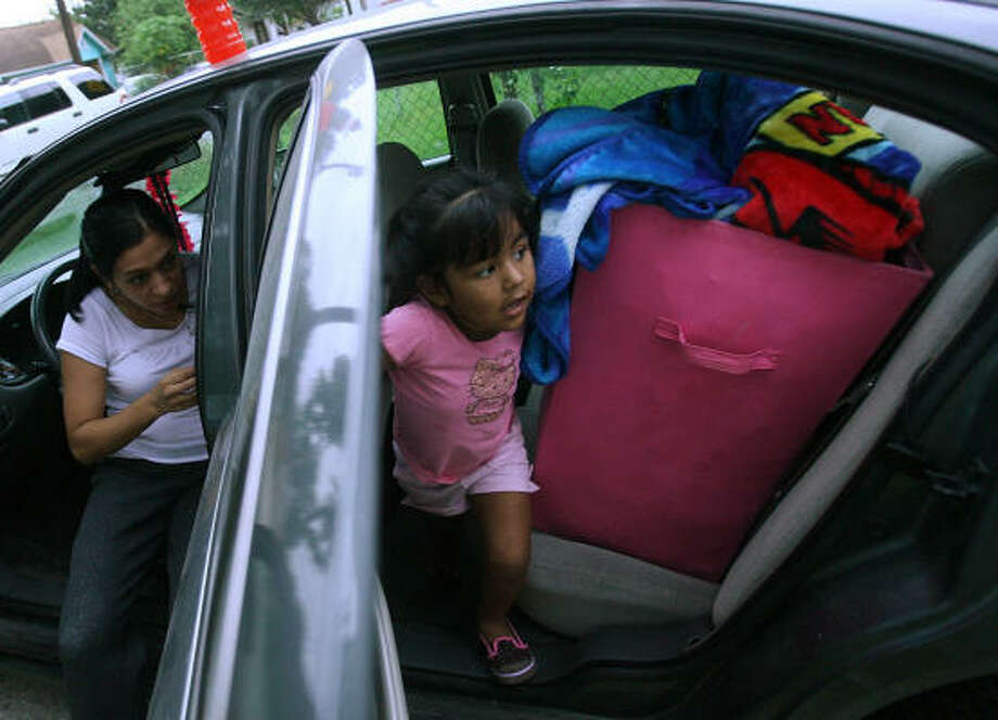 Stephanie Hernandez and daughter Jordan Martinez load up the car to leave Manchester. Photo: Mayra Beltran, Chronicle