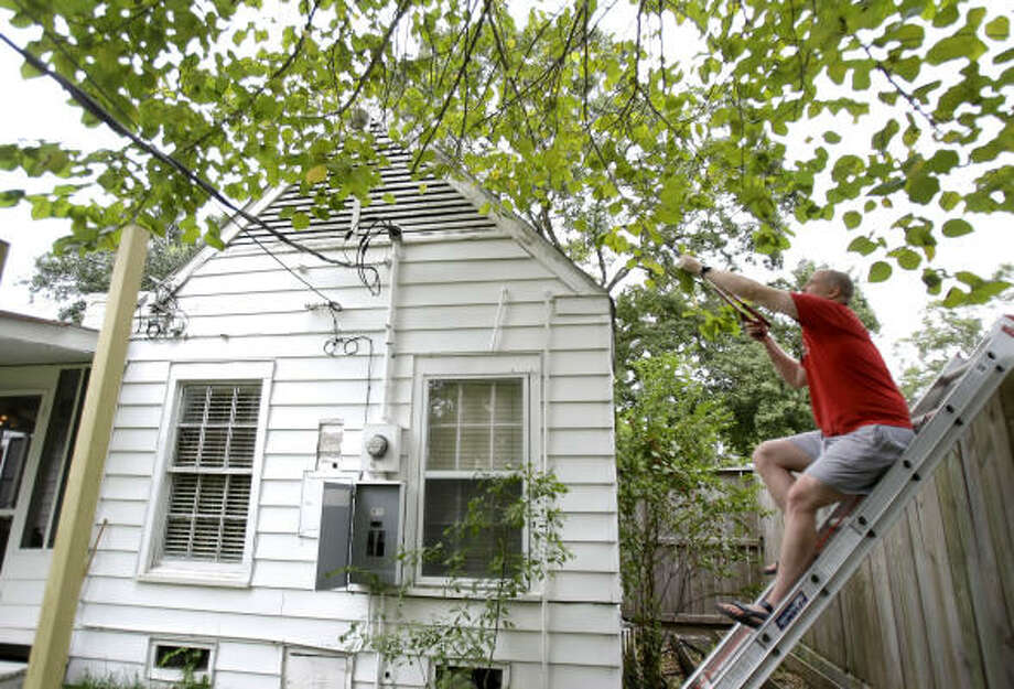 Worried about Hurricane Ike, Fred Trotter tries to reach tree branches that were dipping close to power lines at his home near the University of Houston Friday. Photo: Karen Warren, Chronicle