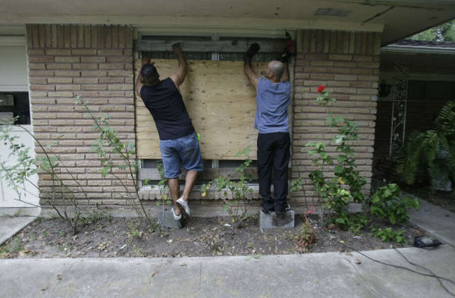 David Silva, left, and his brother, Rey Silva, right, cut scrap boards to put on the windows at their mother's house near Houston's Hobby Airport. Photo: Karen Warren, Chronicle