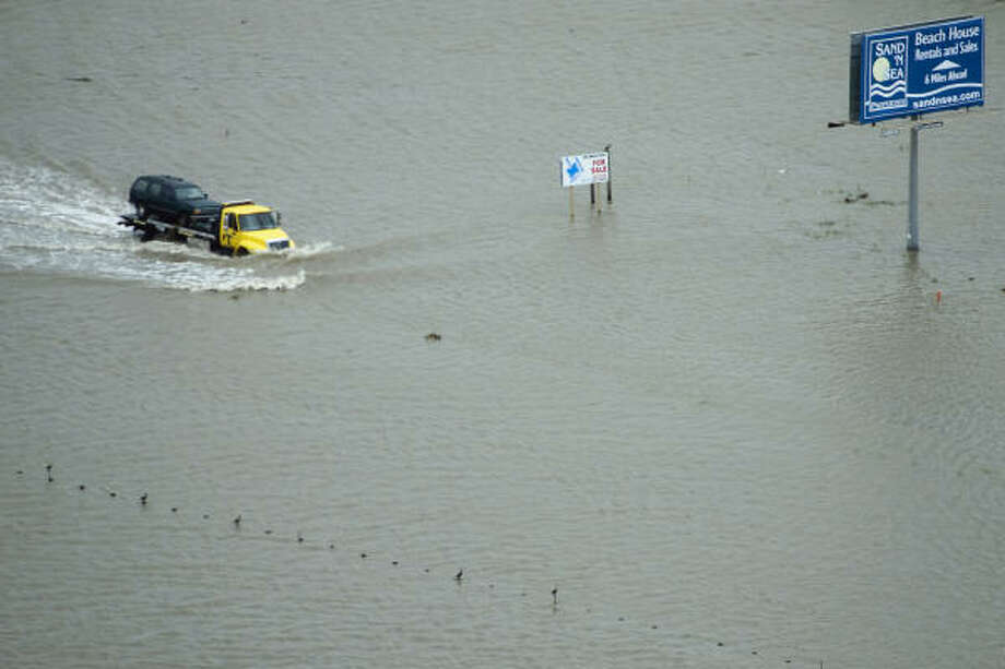 A truck drives through floodwaters on the road at  San Luis Pass on Galveston Island. Photo: Smiley N. Pool, Chronicle