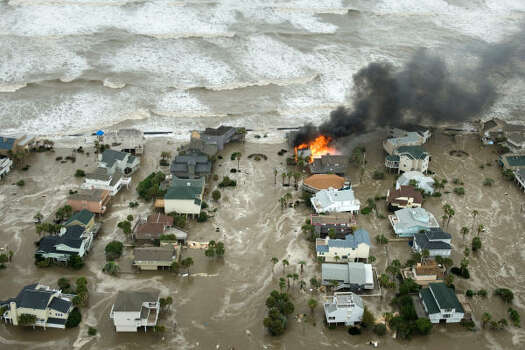 A house is engulfed in flames as floodwaters and crashing waves inundate beach homes on Galveston Island Friday. Photo: Smiley N. Pool, Chronicle