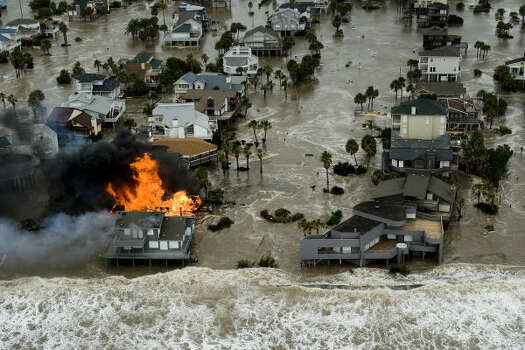 A fire destroys a house as water threatens Galveston Island homes. Photo: Smiley N. Pool, Chronicle