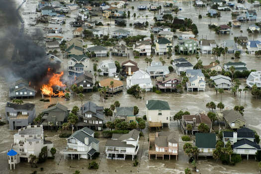 Flames destroy a Galveston house as floodwaters rise. Photo: Smiley N. Pool, Chronicle