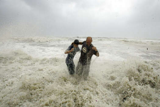 Steve Owen, right, and his son Austin Owen, 13, are swamped by a wave in Galveston. Photo: LM Otero, AP