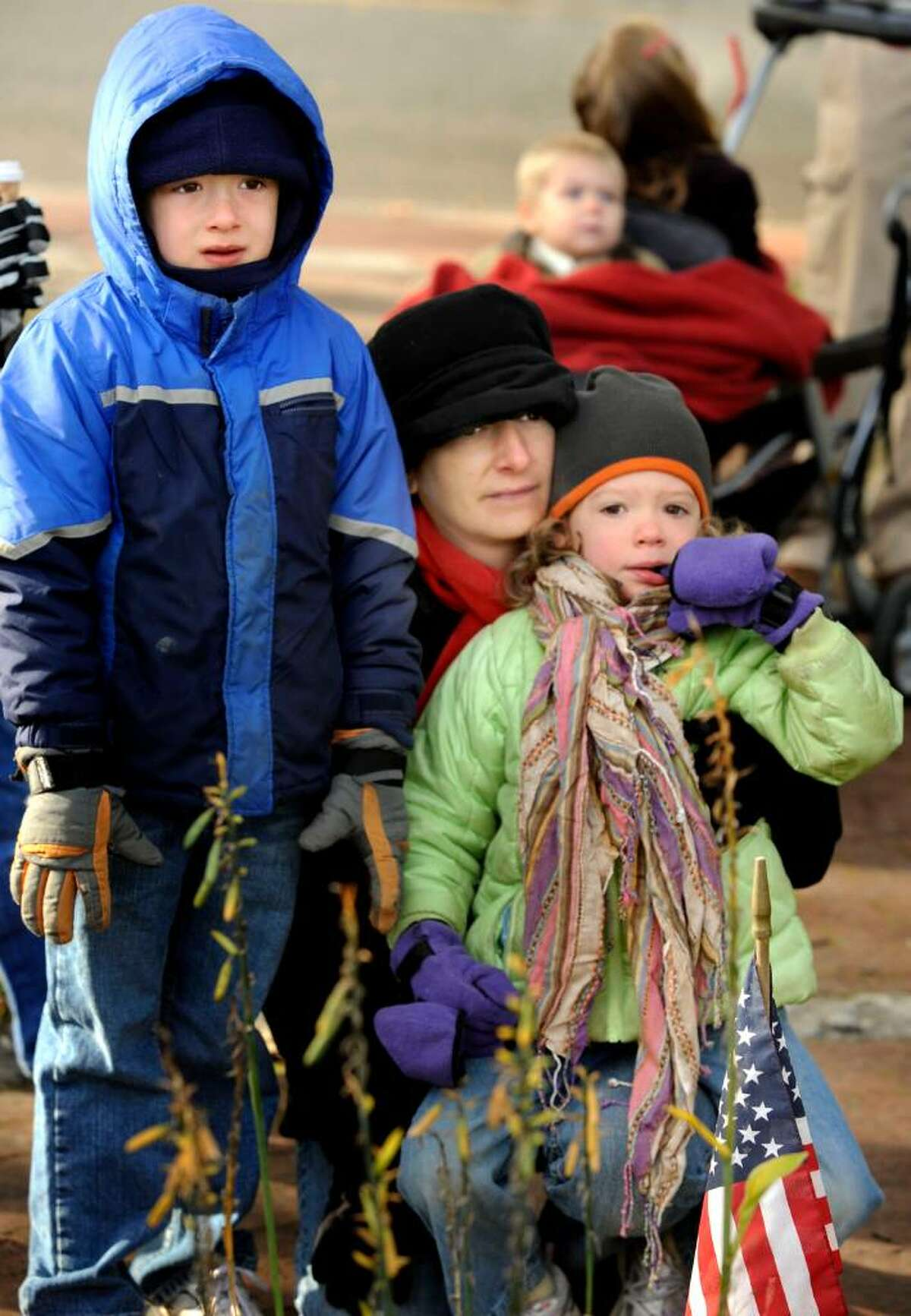 Mason Baliko, 6, his mother, Allison Valentino, and sister, Madeleine Baliko, 4, of Bethel, listen to speeches at P.T.Barnum Square during the Bethel Columbus Day Parade on Monday, Oct.12,2009.