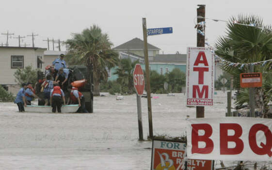 Rescuers help Dondi Fields, 50, climb onto a truck as she, her husband, David Fields, 45, and their dog leave their Surfside Beach home. Earlier in the day, David Fields refused assistance from officials who wanted to evacuate them. Photo: Julio Cortez, Chronicle