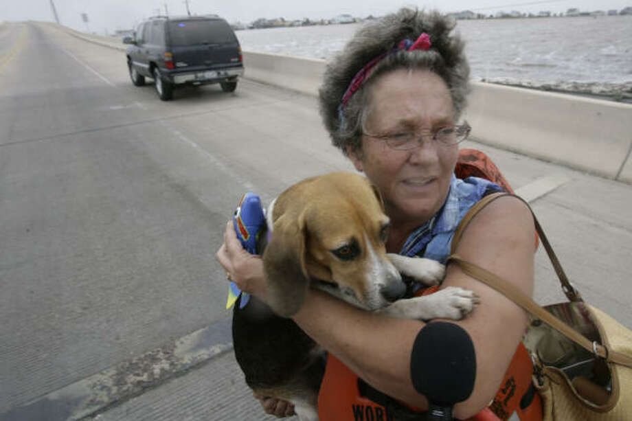 Dondi Fields, 50, holds on to her dog Sandy Beach Friday after they, along with her husband, David, were rescued from their home at Surfside Beach. Earlier in the day, David Fields denied offers of assistance from officials trying to get them to evacuate. Photo: Julio Cortez, Chronicle