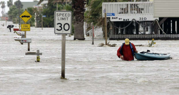 Bobby Taylor uses a kayak to evacuate as his neighborhood was overtaken by water in Surfside Beach. Photo: Eric Gay, AP