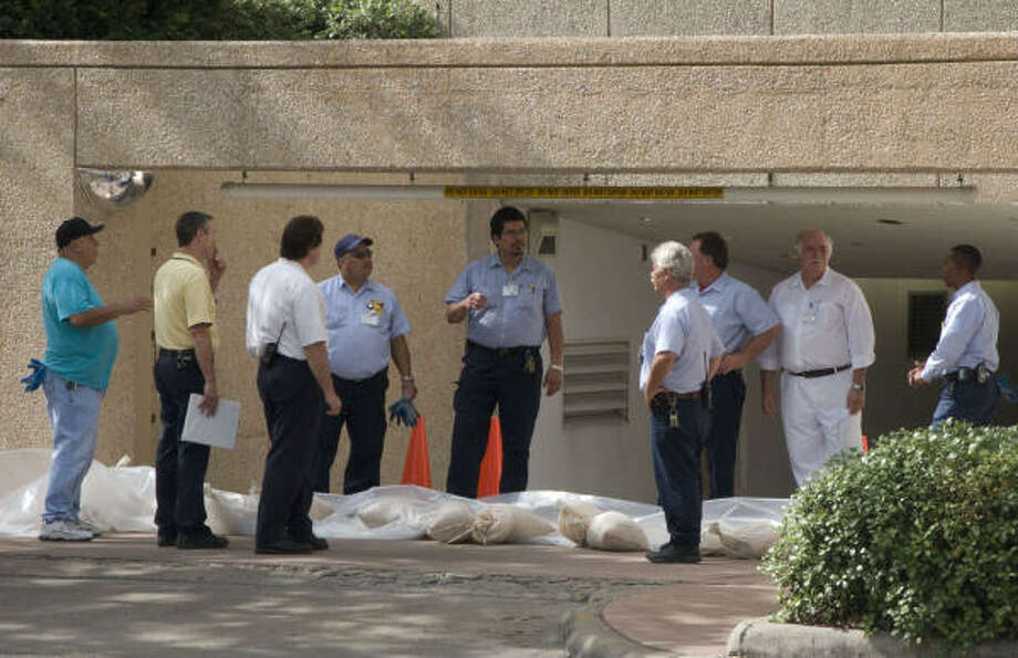 Workers get instructions for sandbagging the entrance to an underground parking garage at Houston's