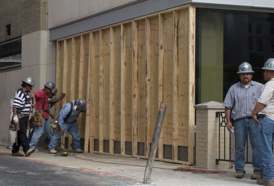 Workers board up large plate glass windows of a restaurant on Fannin at the Texas Medical Center Friday. Photo: Steve Ueckert, Chronicle