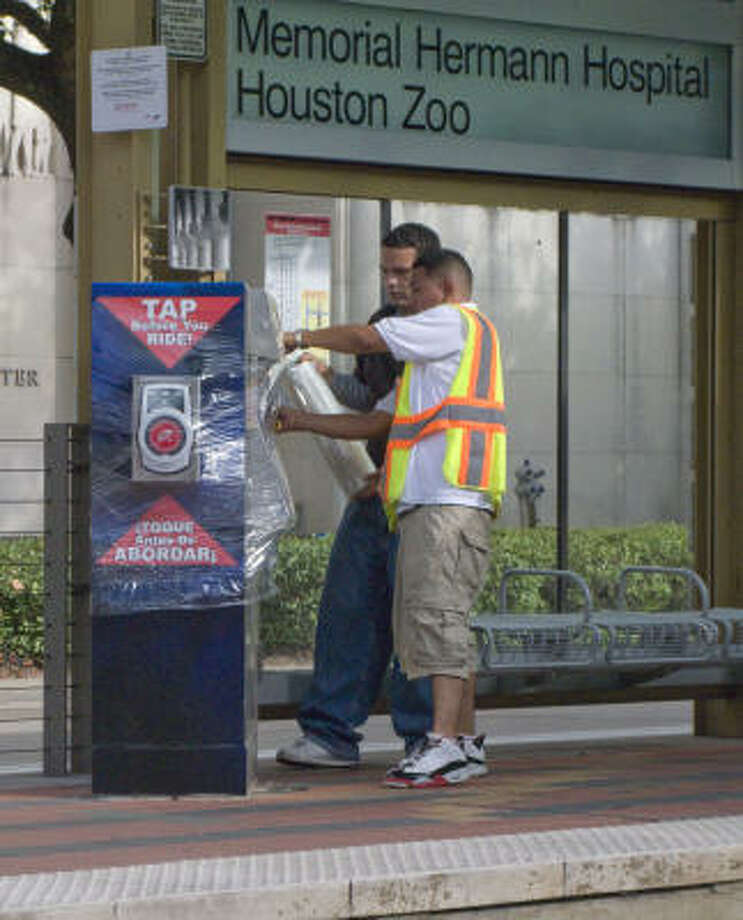 Metro employees shrinkwrap ticket kiosks in the Texas Medical Center Friday. Photo: Steve Ueckert, Chronicle