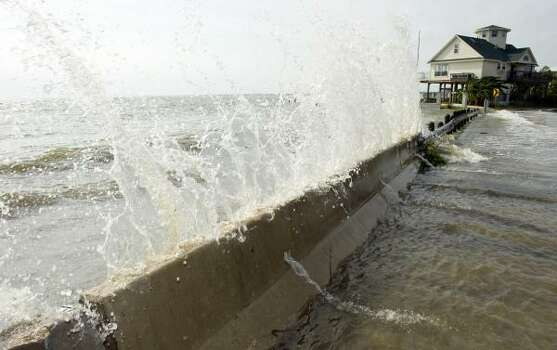Water from Galveston Bay crashes over a barrier in Seabrook Friday. Photo: Dave Einsel, Getty Images