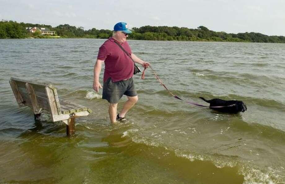 Jeff Brummerhop walks his dog Skeeta through high waters in Seabrook Friday. Photo: Dave Einsel, Getty Images