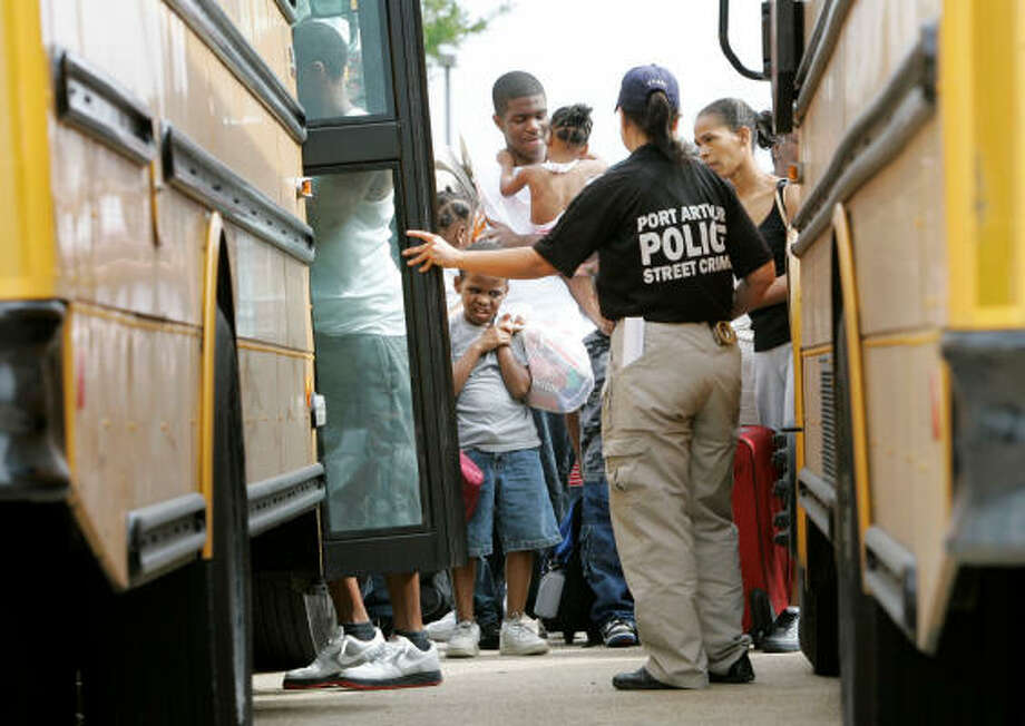 A Port Arthur police officer assist evacuees onto a waiting school bus Friday. Officials expect much of Port Arthur to flood from Ike's storm surge. Photo: Tony Gutierrez, AP